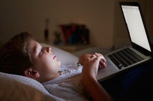 Boy Using Laptop In Bed At Night