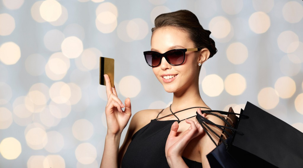sale, finances, fashion, people and luxury concept - happy beautiful young woman in black sunglasses